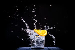 splash of water in drinking glass with sliced lemon
